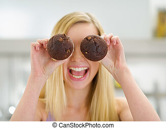 Happy teenager girl holding chocolate muffins in front of...