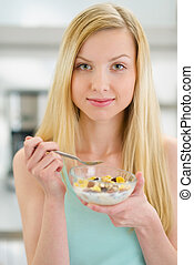 Teenager girl eating flakes with milk in kitchen
