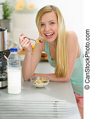 Smiling teenager girl having breakfast eating flakes with...