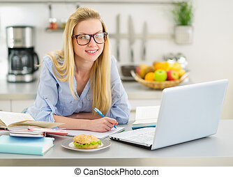 Happy teenager girl studying in kitchen