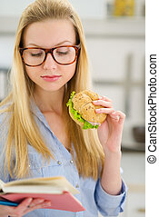 Young woman eating sandwich and reading book