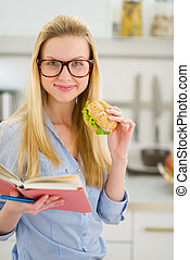 Happy teenager girl eating sandwich and reading book
