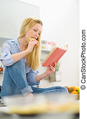 Young woman eating sandwich and reading book in kitchen