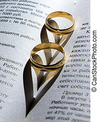 wedding ring on a book with a shadow in the shape of a heart