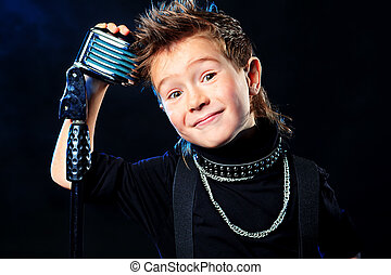 smiling boy - An emotional little boy is singing into a...