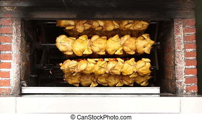 whole chickens roasting in a shop oven, mexico