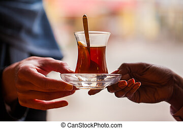 oriental tea-time - hands passing a glass of Turkish tea