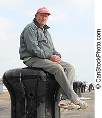sitting on a capstan - A white male sitting on a capstan on...