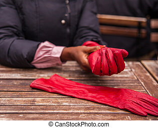red gloves - woman putting on red gloves