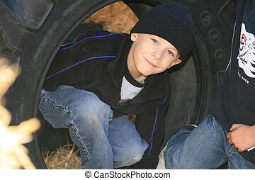 6 year old boys playing in a tire