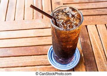 Fresh black soda with ice on wood table