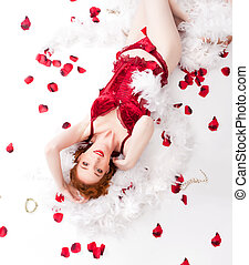 redhaired woman wearing red lingerie with rose petals and...