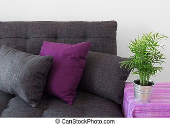 Cozy sofa with cushions and green plant