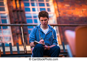young man writing in a book