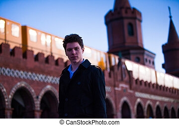 young man - male teenager in front of the Oberbaum bridge in...