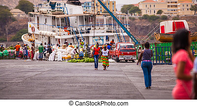 two women walking along the busy harbor