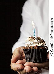 Happy Birthday - A Man holding a cupcake with a candle in a...