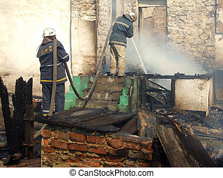 Smoldering remains of a ghetto house with a fireman spraying...