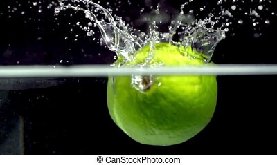 fresh lime fruit dropped into water shot in super slow...