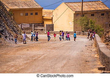 children playing on a dusty street of a small village