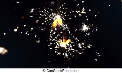 a sparkler being ignited making abstract pattern shot in...