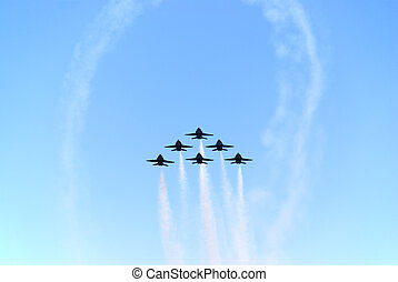 air show - a formation of airplanes on a blue sky
