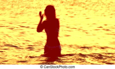 woman dances alone in the sea at sunset
