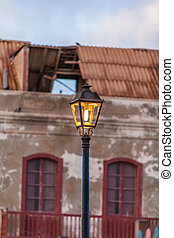 lamppost with broken orange glazing in front of a ruin