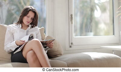 a pretty businesswoman reads, relaxing, or awaiting an...