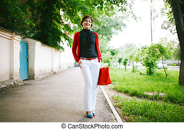 A young asian woman in red smiles in an outdoor setting.