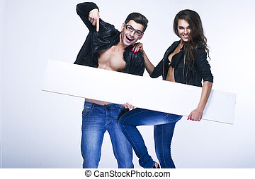 Fashionable happy couple holding white board
