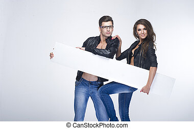 Fashionable lovely couple holding white board