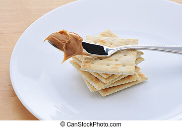 Peanut Butter on knife resting on a stack of crackers