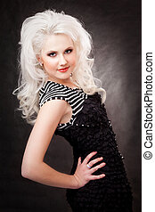 studio shot of a young, beautiful, blonde woman in black dress