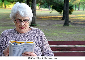 Senior Woman working a puzzle book.