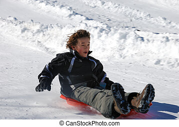 Boy Sledding Fast Down the Hill on a Red Sled - boy sledding...