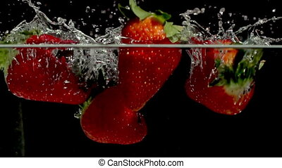 fresh strawberry fruit dropped into water shot in super slow...