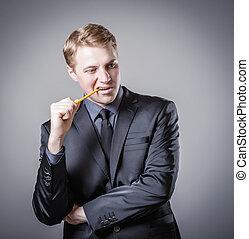 Young man biting a pencil