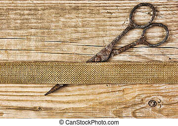 old tailor scissors and belt on the wooden background