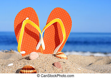 Flip-flops - Orange flip-flops in sand on the beach in...