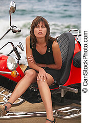 Young beautiful woman sits on trike near to the sea