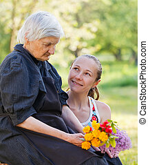 Elderly woman get flowers from her grandchild