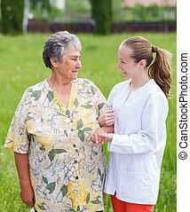 Elderly care - Elderly woman with her caretaker walking in...