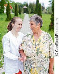 Elderly care - Elderly woman with her caretaker walking in...