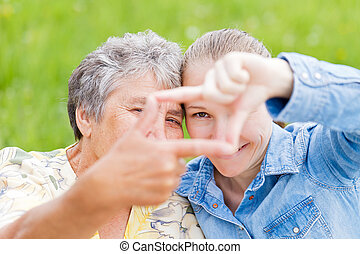 Elderly woman and her daughter framing their faces