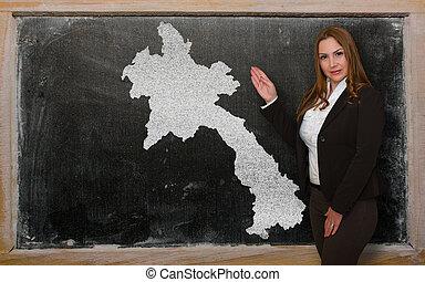 Teacher showing map of laos on blackboard