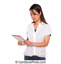 Charming young woman reading on tablet pc screen - Portrait...