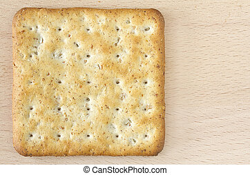 One wholegrain cracker on wooden board