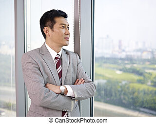 asian businessman looking out of window in office.
