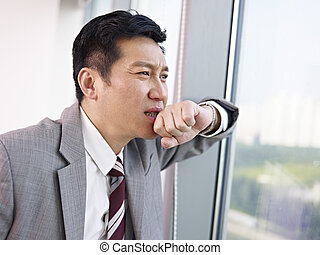 asian businessman - troubled asian businessman looking out...